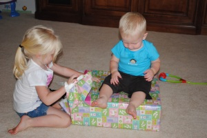 Ethan helping Sophie open her presents...